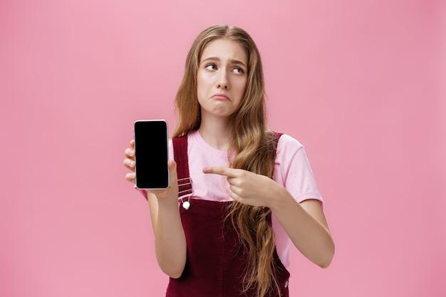 Мрачная недовольная и разочарованная симпатичная молодая девушка держит смартфон в помещении, указывая на цел ...