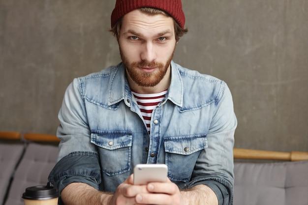 携帯電話を保持している流行の服で見栄えの良いひげを生やしたヒップスターの室内撮影