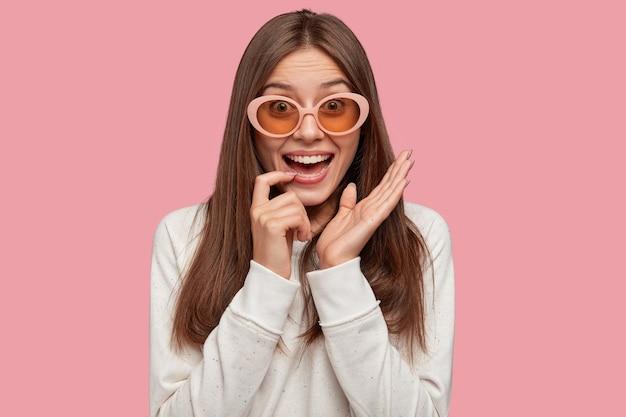 格好良い陽気な若い女性の屋内ショットは人差し指を口の近くに保ちます