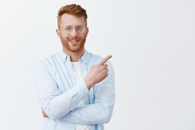 Снимок в помещении: симпатичный, уверенный в себе и властный мужчина-предприниматель в рубашке и очках с рыжими волосами, указывающий на правый верхний угол и ухмыляющийся