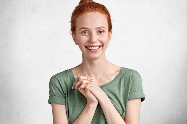 Снимок в помещении красивой счастливой девушки-модели, которая держит руки вместе, сияет улыбкой, носит повседневную одежду и рада