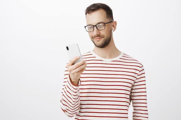眼鏡をかけた、リラックスしたヨーロッパ人の素敵な室内ショット、スマートフォンを持ち、聴く曲を選ぶ、ワイヤレスイヤホンを着用