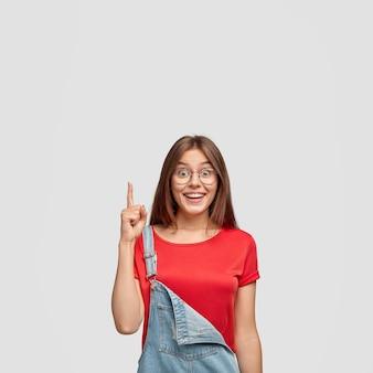 見栄えの良い満足しているブルネットの女性の屋内ショットは、顔の表情を喜ばせ、素晴らしいアイデアを念頭に置いています