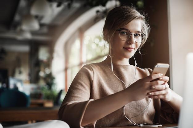 안경에 공정한 머리카락을 가진 잘 생긴 세련되고 행복한 백인 여성의 실내 샷, 스마트 폰을 들고 비디오를 보면서 이어 버드를 착용하고 외모와 미소를 산만하게합니다. 무료 사진