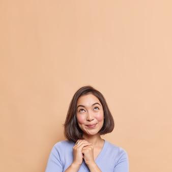 黒髪の東部の外観を持つ格好良い若い女性の屋内ショットは、希望に満ちた夢のような表情で手を一緒に見せますベージュの壁に隔離されたカジュアルなジャンパーを着ています