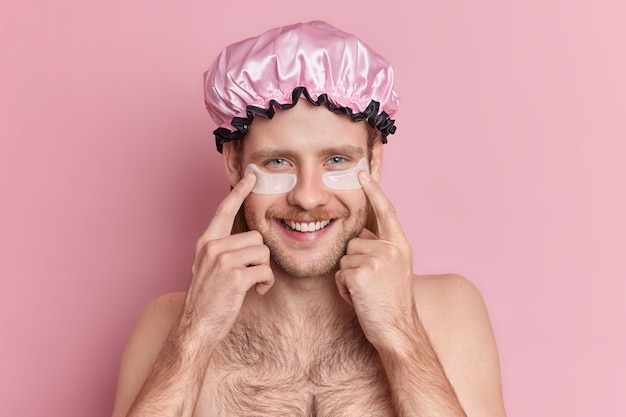 수염을 가진 잘 생긴 웃는 젊은 남자의 실내 촬영은 눈 아래 하이드로 겔 패치를 나타냅니다. 무료 사진