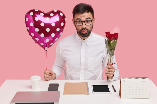 Снимок в помещении: красивый небритый мужчина надувает губы, несет валентинку и букет, имеет романтические отношения в офисе, позирует над розовой стеной студии