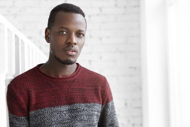 Снимок красивого молодого афроамериканца в помещении, одетого в уютный свитер из джерси