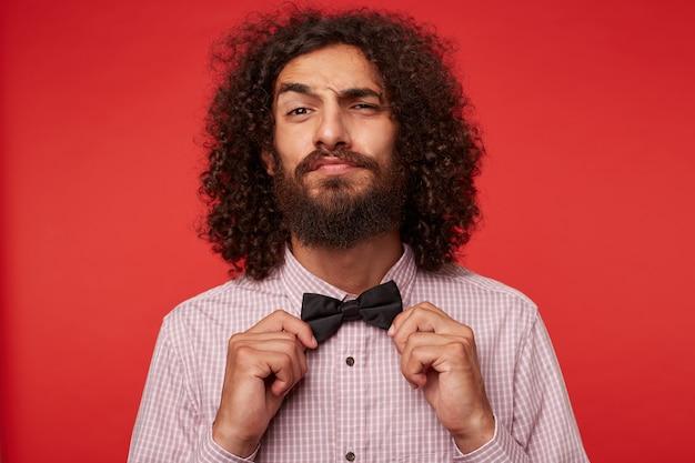 Снимок в помещении: красивый молодой кудрявый бородатый мужчина с длинными темными волосами держит руки на галстуке-бабочке, поднимает бровь и смотрит в камеру со скругленными губами, изолированно на красном фоне