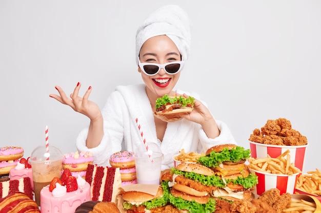 행복한 아시아 여성의 실내 사진은 진심으로 맛있는 햄버거를 들고 손을 미소 짓습니다