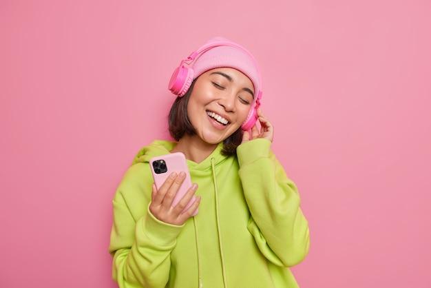 幸せなアジアの女性の屋内ショットは頭を傾けますプレイリストからお気に入りの音楽を聴きますステレオヘッドフォンを着用します携帯電話を着用しますカジュアルな緑のスウェットシャツとピンクの壁に隔離された帽子を着用します