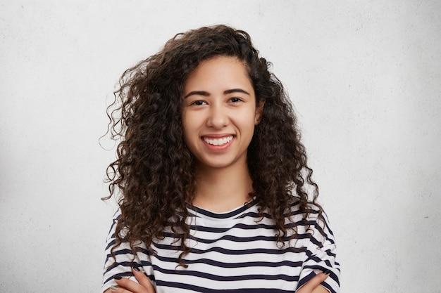 Крытый снимок счастливой красивой женщины с вьющимися густыми темными волосами, здоровой чистой кожей, широкой улыбкой и белыми ровными зубами