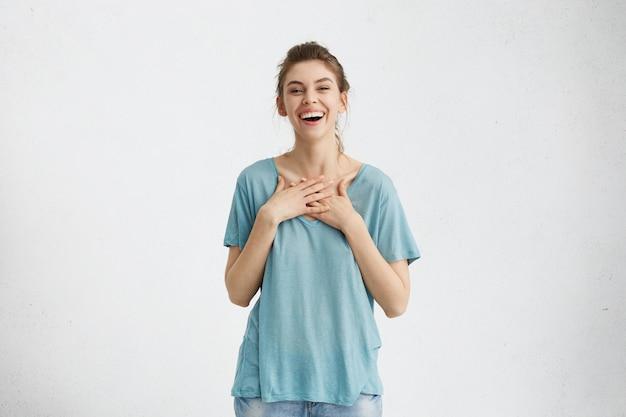 행복 한 아름 다운 여자의 실내 샷 머리 롤빵 유쾌 하 게 웃 고, 기쁘게 그녀의 가슴에 손을 유지