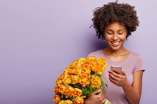 생일 축하 여자의 실내 촬영은 특별한 날을 축하하고, 오렌지 꽃다발을 보유하고 있습니다.