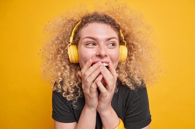 행복한 곱슬머리 여성의 실내 사진은 낄낄거리며 손으로 입을 가리고 무선 헤드폰을 끼고 음악 감상을 즐긴다