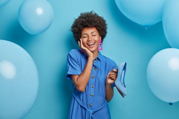 Снимок в помещении: счастливая кудрявая женщина веселится, одеваясь для тематической вечеринки, выбирает туфли по размеру платья, нежно касается лица, закрывает глаза и смеется, позирует
