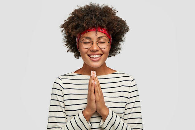 Снимок в помещении: счастливая, довольная улыбающаяся женщина, мечтающая о многом, позирует в молитвенном жесте и загадывает