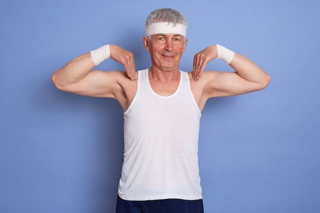 Снимок в помещении счастливого энергичного пожилого мужчины, наслаждающегося физической подготовкой у синей стены, выполняющего физические упражнения, держащего пальцы на плечах