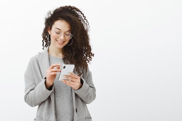 Крытый снимок счастливой модной женщины с модными серьгами и очками, стоящей в сером пальто
