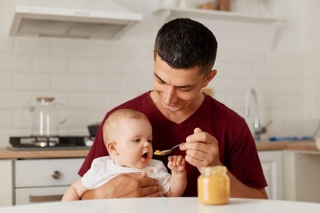 Крытый снимок счастливого отца, сидящего за столом с маленькой девочкой на руках и кормящего дочь фруктовым или овощным пюре, прикорма ребенка.