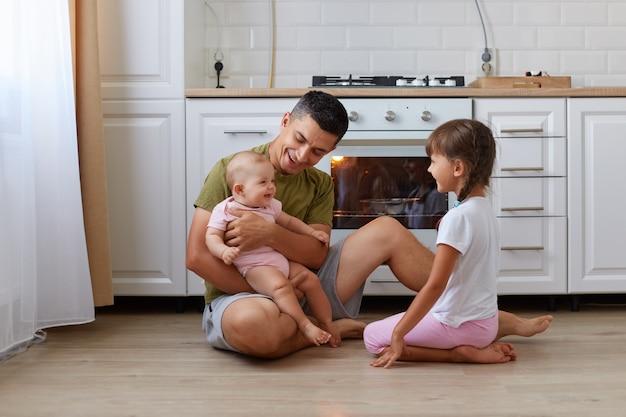 Крытый снимок счастливого красивого брюнетного мужчины в повседневной одежде, сидящего на полу на кухне со своими детьми, держащего в руках своего малыша и смеющегося.