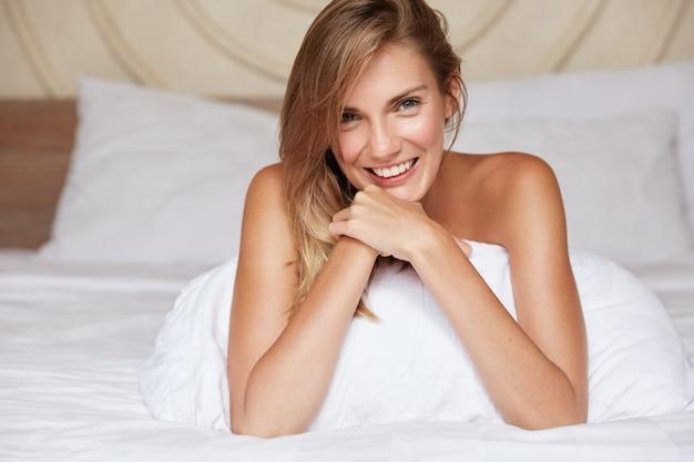 Снимок в помещении: счастливая милая женщина с приятной внешностью лежит на удобной кровати и белом постельном белье, чувствует себя свежей после долгого сна и хороших снов, наслаждается выходными или выходным. концепция сна
