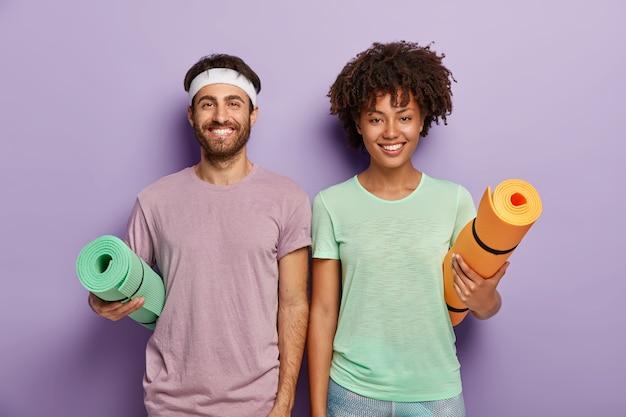 피트니스 훈련 준비가 된 행복한 혼혈 여성과 남성의 실내 샷, 팔 아래에 말아 올린 매트를 들고, 즐거운 얼굴을하고, 활동적인 삶과 일상적인 운동을 즐기고, 캐주얼 한 스포츠 복장을 착용하십시오.