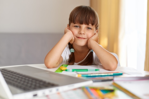 Снимок счастливого и позитивного ребенка женского пола, который смотрит в камеру с оптимистичным выражением лица, делает домашнее задание, любит онлайн-уроки во время карантина.