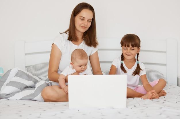 검은 머리를 한 행복한 긍정적인 여성이 아이들과 함께 침대에 앉아 있는 실내 사진, 두 명의 어린 소녀들이 혼, 프리랜서, 육아로 일하려고 노력하고 있습니다.