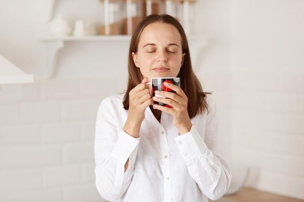 朝、キッチンでコーヒーやお茶を楽しんだり、温かい飲み物を飲んだり、目を閉じてリラックスした表情で立っている幸せなきれいな女性の屋内ショット。