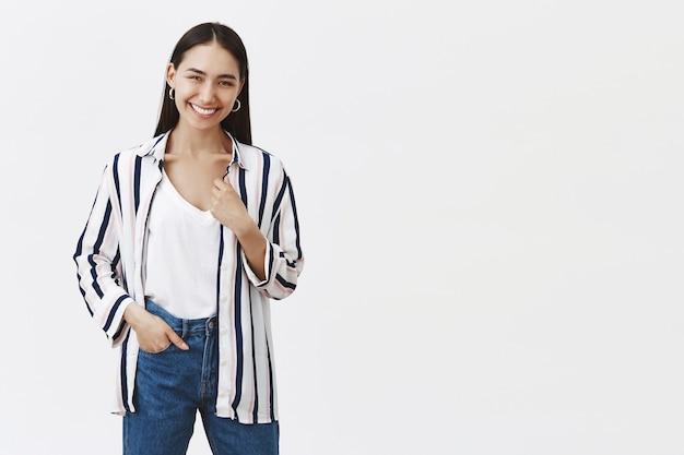 縞模様のブラウスとジーンズで幸せな成功した若い女性起業家の屋内ショット、ポケットに手を握って、嬉しそうに笑って、灰色の壁を越えて自分のビジネスを開いた後に喜んでいる