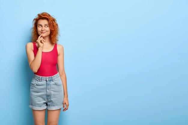 生姜髪の幸せな女性の屋内ショットは、カジュアルなベストとデニムのショートパンツを着て、思いやりのある表情をしていて、何か楽しいものを想像しています