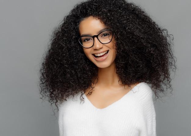 행복한 젊은 아가씨의 실내 샷은 아프로 헤어 스타일을 가지고 있으며, 넓게 미소 짓고 승진을 기뻐하며 광학 안경과 흰색 스웨터를 착용합니다.