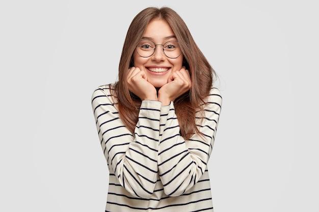 Крытый снимок счастливой молодой женщины в очках, позирующей у белой стены