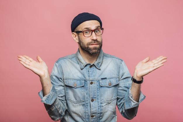 ためらいのあるひげを生やした男の屋内ショットは肩をすくめ、不確かに見え、決定を下すときは疑う