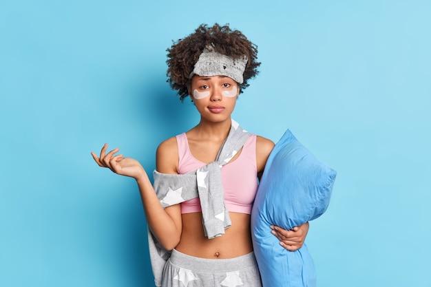 Снимок в помещении нерешительной озадаченной женщины, поднимающей руки с невежественным выражением лица спереди, одетой в ночное белье, держит мягкую подушку, изолированную от синей стены