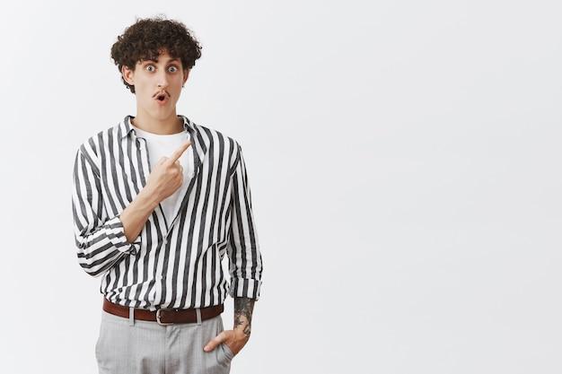 Снимок впечатленного и изумленного еврейского кудрявого парня с усами и татуировками, который отвисает челюсть и задыхается от интереса и волнения, указывает на заинтригованный верхний правый угол.