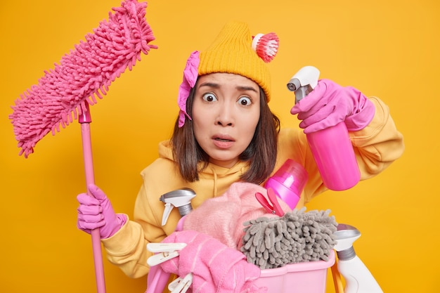 印象的なアジアの女性の屋内ショットは非常に汚れた表面で困惑しているように見えますディスペンサーを使用します週末の春の掃除の前に休日はモップを使用して床を洗うスウェットシャツの帽子の手袋を着用します