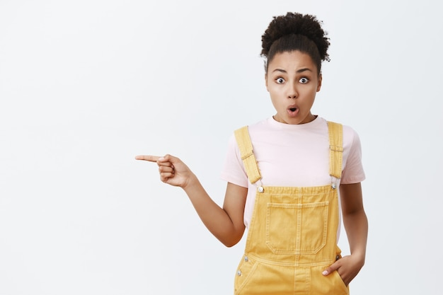 Снимок впечатляющей выразительной симпатичной афроамериканки в желтом комбинезоне в помещении, отвисающей от удивления челюсти, складывающейся губами и указывающей на место для текста слева над серой стеной