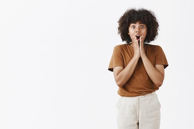 Внутренний снимок впечатленной безмолвной красивой африканской женщины с вьющейся стрижкой, держащей ладони на лице, в изумлении отвисшей челюсти, стоящей с возбужденным ртом над серой стеной