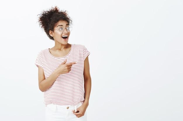 Крытый снимок впечатленной женщины с афро-прической, позирующей в студии