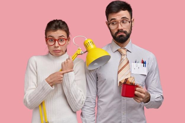 Снимок возмущенной европейской женщины в помещении, держащей желтую настольную лампу, которая вместе с красивым парнем держит кружку свежего напитка, вместе учится