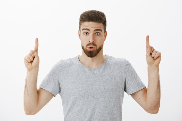 ひげと茶色の髪型で唇を折りたたみ、驚きと好奇心を育てる人差し指で灰色の壁に疑問を投げかける興味深く興味をそそられるハンサムな男性の室内撮影