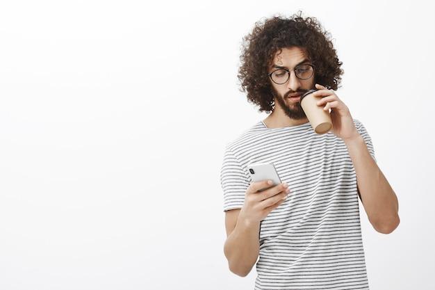 トレンディなメガネとストライプのtシャツを着た興味のあるハンサムな男性の男子生徒の屋内ショット、新しい白いスマートフォンでメッセージを送信、カップからコーヒーを飲む
