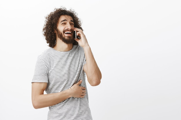 Снимок в помещении: радостный привлекательный парень с бородой и афро-прической смотрит в сторону, разговаривает по смартфону и громко смеется