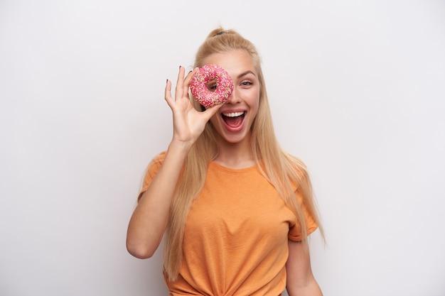白い背景の上に分離されたカメラを元気に見ながら、上げられた手でドーナツを楽しんでいるカジュアルな髪型の楽しい魅力的な若いブロンドの女性の屋内ショット