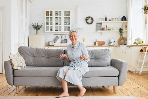 Крытый снимок радостной очаровательной пожилой домохозяйки в стильном платье, сидящей на большом сером диване босиком на полу с сияющей улыбкой, эмоционально жестикулирующей и в хорошем настроении