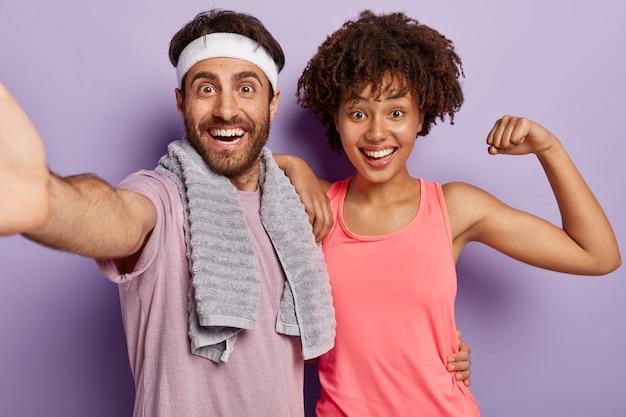 楽しい多様なカップルの屋内ショットは、筋肉を柔軟に保ち、毎日のトレーニングを行い、スポーツウェアを着用し、幸せな表情でカメラをよく見てください