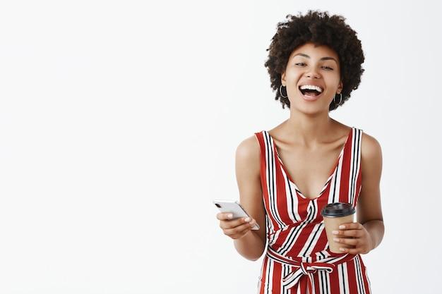 Крытый снимок радостной, эмоциональной красивой африканской женщины с афро-прической, радостно смеющейся над забавной шуткой, держащей бумажный стаканчик и веселым смартфоном