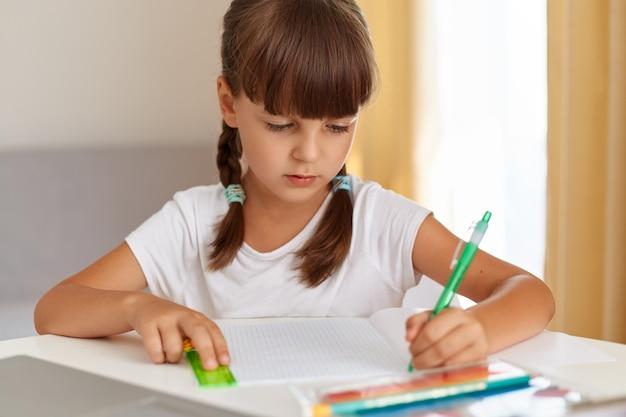 Снимок в помещении маленькой симпатичной сконцентрированной девочки в белой футболке с темными волосами и косичками, которая делает домашнее задание дома, пишет в тетради.
